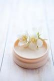 Crème avec la fleur de jasmin sur la table en bois blanche Photos stock