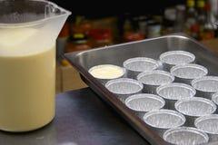 Crème brulée dans le processus sur des moules de bidon Photographie stock