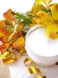 Crème cosmétique avec des fleurs photographie stock