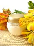 Crème cosmétique avec des fleurs Photographie stock libre de droits