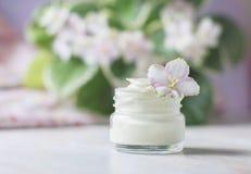 Crème cosmétique avec des fleurs sur un fond en pierre clair Photo stock