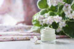 Crème cosmétique avec des fleurs sur un fond en pierre clair Images stock