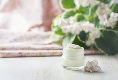 Crème cosmétique avec des fleurs sur un fond en pierre clair Photographie stock