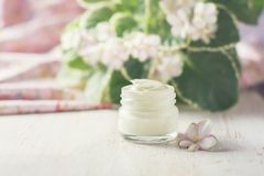 Crème cosmétique avec des fleurs sur un fond en pierre clair Image libre de droits