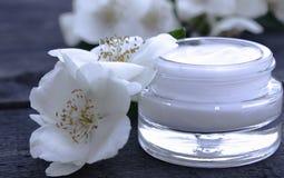 Crème cosmétique dans un pot en verre avec des fleurs de jasmin sur un fond en bois photos libres de droits