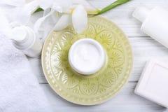 Crème cosmétique de plat et d'autres accessoires de bain sur l'étiquette en bois Photos stock