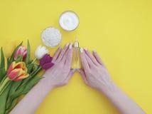 Crème cosmétique, mains sur le papier coloré jaune photos stock