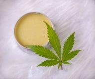 Crème de chanvre de cannabis avec la feuille de marijuana au-dessus du fond blanc photographie stock