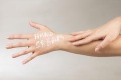 Crème de main en main Photographie stock