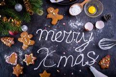 Crème de meringue de vue supérieure marquant avec des lettres le Joyeux Noël sur le fond en pierre noir avec des ingrediens et de Photos libres de droits