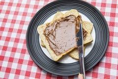 Crème de propagation de chocolat de femme inconnue sur le pain Photo libre de droits