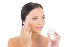 Crème de propagation de beauté de femme de brune sur sa joue Photo libre de droits
