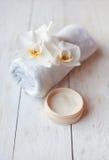 Crème de visage avec l'orchidée et la serviette blanches sur la table en bois blanche Image libre de droits