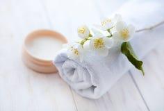 Crème de visage avec la fleur et la serviette de jasmin sur la table en bois blanche Images libres de droits
