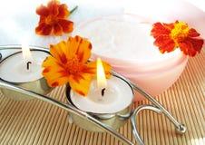 Crème et bougie avec des fleurs photos stock