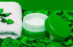 Crème et essuie-main avec les pétales verts Image libre de droits