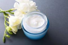 Crème et fleur cosmétiques sur le fond gris Photographie stock libre de droits