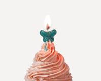 Crème et lueur d'une bougie de petit gâteau Images stock