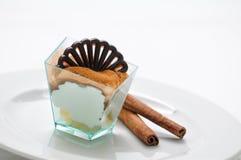 Crème fouettée avec la poudre de cannelle et pomme dans le goûteur, le dessert doux avec de la cannelle et la pomme du plat blanc Photo libre de droits