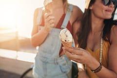 Crème glacée à disposition d'une femme se tenant avec son ami Photographie stock