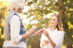 Crème glacée amusée d'échantillon de jeune femme avec la mère âgée dehors Images libres de droits
