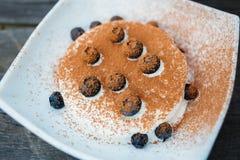 Crème glacée avec des myrtilles et poudre de cacao dans le piala blanc Image stock