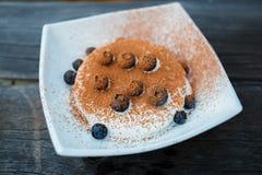 Crème glacée avec des myrtilles et poudre de cacao dans le piala blanc Photo libre de droits