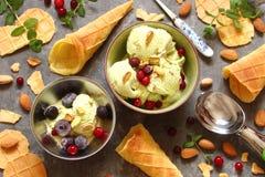 Crème glacée avec des pistaches et des cornets de crème glacée, avec des baies, minute Photos stock