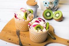 Crème glacée délicieuse dans une tasse avec les fruits savoureux Photographie stock libre de droits