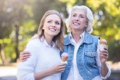 Crème glacée d'échantillon de femme agée avec la fille en parc Images stock