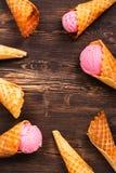 Crème glacée dans des cônes de gaufre au-dessus de fond en bois Photo stock