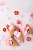 Crème glacée dans un cône de gaufre sur un fond clair Crême glacée de fraise Fleurs dans un cône de gaufre Oeillets roses Fleurs  photos libres de droits