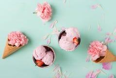 Crème glacée dans un cône de gaufre sur un fond de turquoise Crême glacée de fraise Fleurs dans un cône de gaufre Oeillets roses images libres de droits