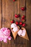 Crème glacée dans un cône de gaufre sur un fond en bois Crême glacée de fraise images libres de droits