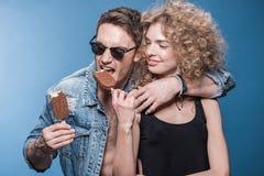 Crème glacée mangeuse d'hommes chez la main du ` s de la femme sur le bleu Images libres de droits