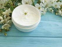 Crème hydratante cosmétique crème nourrissant la cerise de floraison saine de traitement organique sur un fond en bois bleu Photos stock