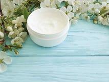 Crème hydratante cosmétique crème nourrissant la cerise de floraison saine de traitement organique sur une protection en bois ble Photographie stock libre de droits