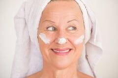 Crème hydratante mûre de visage de femme d'Attracive Photo stock