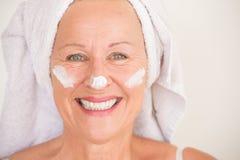 Crème hydratante mûre joyeuse de visage de femme Photographie stock