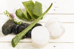 Crème hygiénique cosmétique de Vera Herbal d'aloès avec les fleurs blanches et roses avec la roche noire sur le fond blanc en boi photos stock