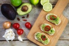 Crème ou guacamole d'avocat sur les canapes et les ingrédients l de baguette Image libre de droits