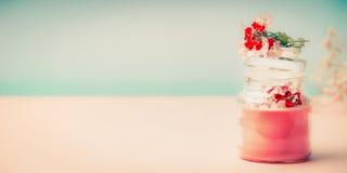Crème rose dans le pot en verre pour des soins de la peau avec des supports de fleurs sur la table au fond de turquoise, vue de f Photo libre de droits