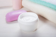 Crème, savon et serviettes cosmétiques sur une fin de table  Images libres de droits