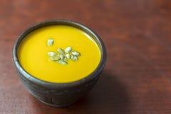 Crème-soupe à potiron avec l'addition des graines de citrouille et des épices, vue de au-dessus de, tir de studio Plat d'argile d photos stock