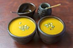 Crème-soupe à potiron avec l'addition des graines de citrouille et des épices, vue de au-dessus de, tir de studio Plat d'argile d images stock
