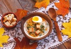 Crème-soupe à potiron décorée des feuilles, de l'oeuf à la coque et du c d'érable image libre de droits