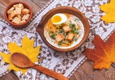 Crème-soupe à potiron décorée des feuilles, de l'oeuf à la coque et du c d'érable image stock