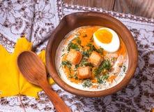 Crème-soupe à potiron décorée des feuilles, de l'oeuf à la coque et du c d'érable photo libre de droits