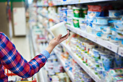 Crème sure d'achats de femme dans le magasin photographie stock libre de droits
