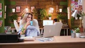 Créateur féminin de médias travaillant sur son ordinateur et se levant pour vérifier son conseil de conception banque de vidéos